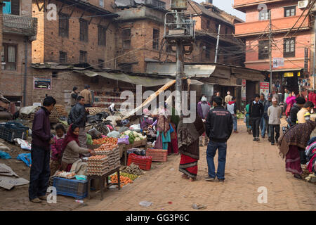 Bhaktapur, Nepal - December 5, 2014: People buying and selling goods at a local market - Stock Photo