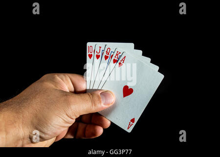 Hand holding poker cards to form a royal flush on black background - Stock Photo
