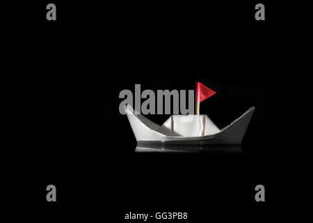 paper boat floating on water on black background with red flag - Stock Photo