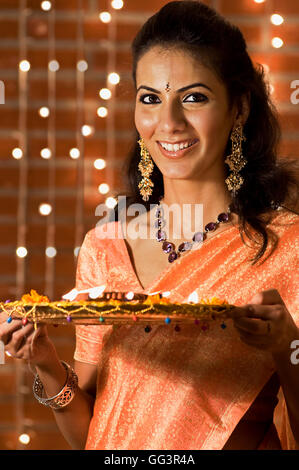 Woman holding a tray of diyas - Stock Photo