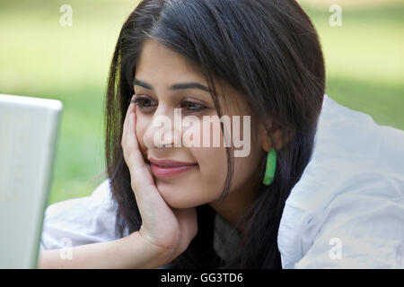Close-up of young woman lying on grass using laptop - Stock Photo