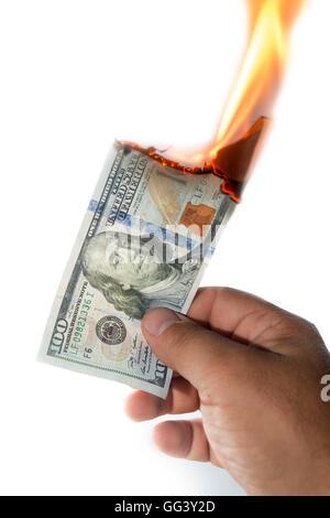 man hand holding a 100 dollars note burning on white background - Stock Photo
