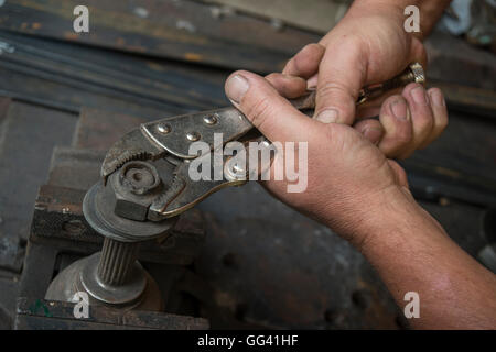 dirty hands of a worker who makes strength on a nut with a clamp - Stock Photo