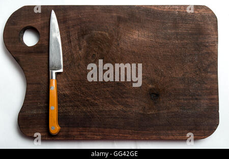 yellow-handled knife on a wooden board on white background - Stock Photo