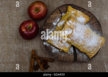 Apple strudel on wooden end of a tree with apples, cinnamon and star anise - Stock Photo