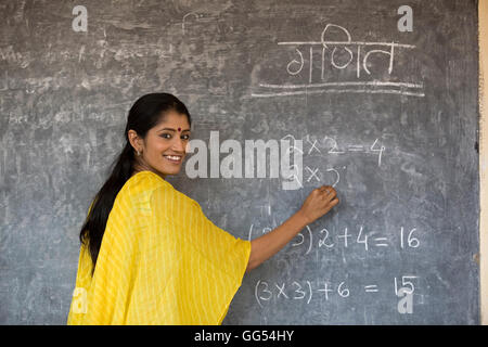 Rural teacher writing on the board - Stock Photo
