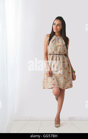 Full length of beautiful young woman in sundress leaning against wall - Stock Photo