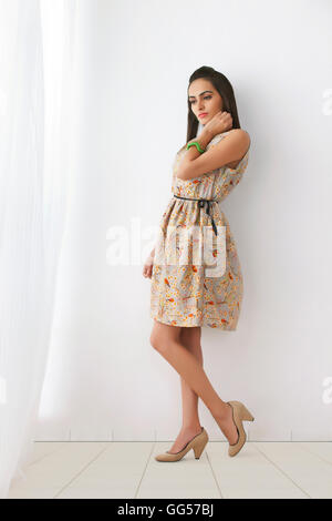 Full length of thoughtful young woman in sundress against white wall - Stock Photo