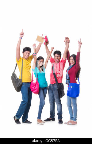 Full length portrait of excited college friends with hands raised against white background - Stock Photo