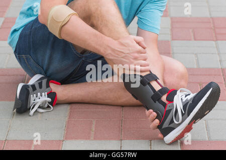 Man in athletic sneakers sitting on the street and checking his ankle orthosis or brace - Stock Photo