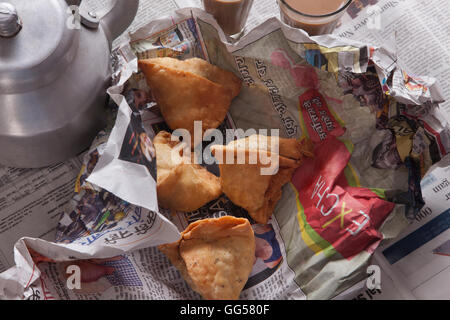 Directly above shot of fresh samosas and tea kettle on table - Stock Photo