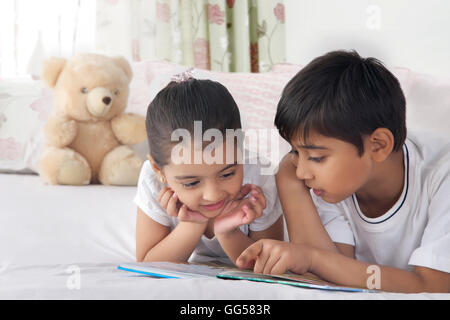 Cute siblings reading book in bed - Stock Photo