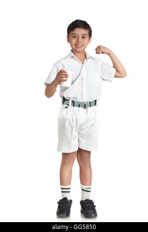 Portrait of boy in school uniform flexing muscles while holding milk over white background - Stock Photo