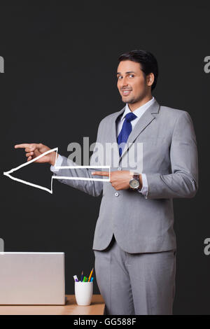 Portrait of young businessman with arrow sign pointing sideways in office - Stock Photo