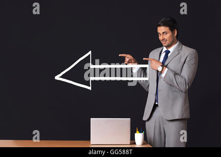 Portrait of Indian businessman with arrow sign pointing sideways in office - Stock Photo