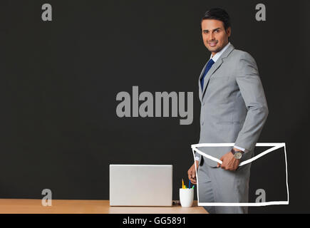 Digitally generated image of Indian businessman holding e-envelope at office - Stock Photo