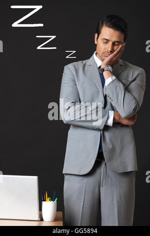 Digitally generated image of young businessman sleeping in office - Stock Photo