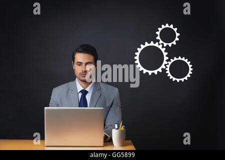 Digitally generated image of businessman using laptop at office desk with gears - Stock Photo