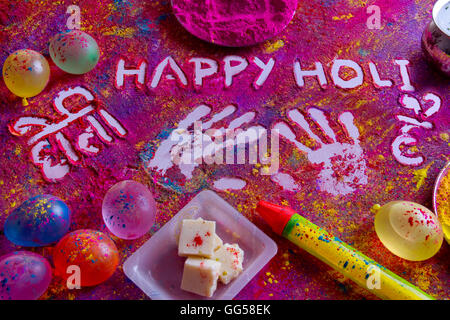 Squirt gun, water bombs, sweet food and colorful Holi power on rangoli - Stock Photo