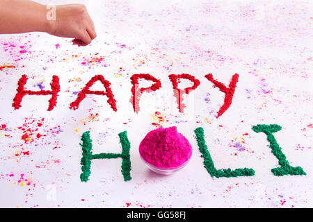 Hand writing HAPPY Holi with gulal over white background - Stock Photo