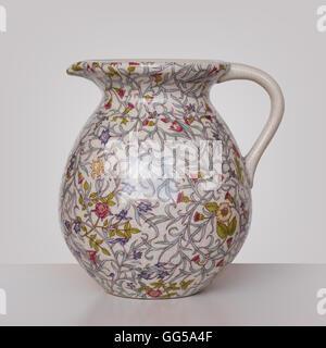 Storage for liquids - Old Vintage colored jug ewer on a light background. - Stock Photo