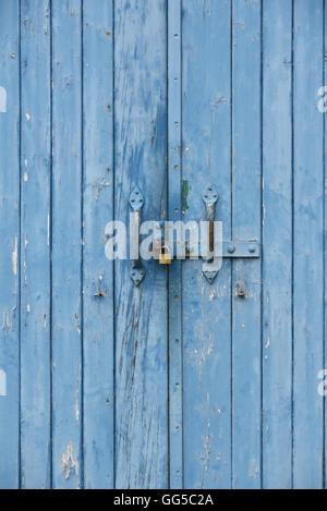 Blue doors with padlock on the door handle - Stock Photo