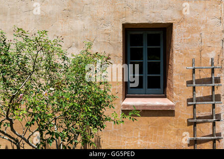 Rustic ladder resting on a old house wall - Stock Photo