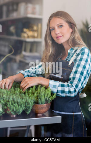 Portrait of a woman arranging potted plants in her shop - Stock Photo