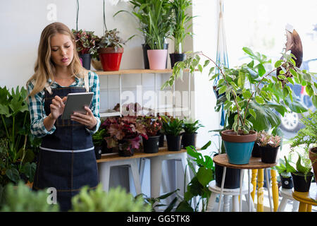 Woman using a digital tablet at her flower shop - Stock Photo