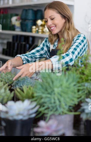 Happy woman arranging plants in her shop - Stock Photo