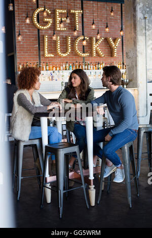 Friends talking at cafe table - Stock Photo