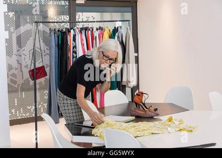 Fashion designer working in her studio - Stock Photo