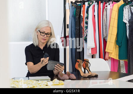 Female dress designer working in her shop - Stock Photo