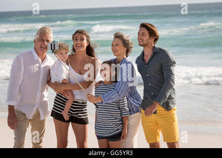 Happy multi-generation family taking selfie together on beach - Stock Photo