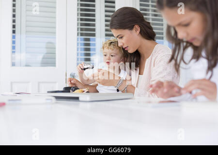 Mother playing with children at home - Stock Photo