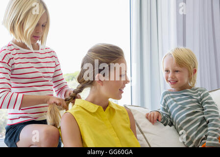 Happy mother and children sitting on couch in living room - Stock Photo