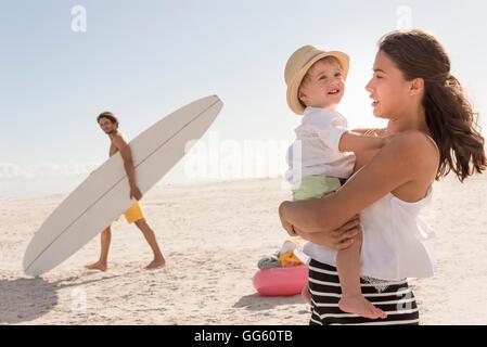 Happy young family enjoying on beach - Stock Photo