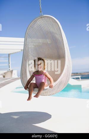 Baby girl sitting in a wicker swing - Stock Photo