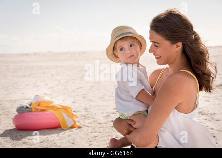 Happy mother with her little son enjoying on beach - Stock Photo