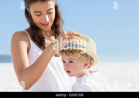 Woman putting hat on her baby head - Stock Photo