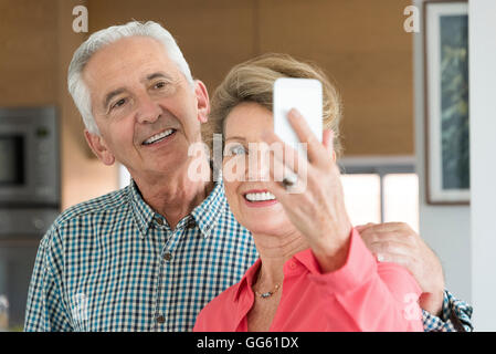 Happy senior couple taking selfie with camera phone - Stock Photo