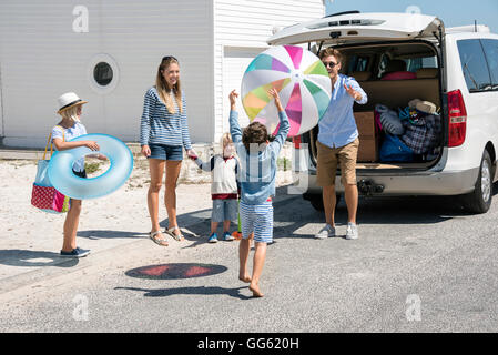 Happy young family packing car with beach gears for vacation - Stock Photo