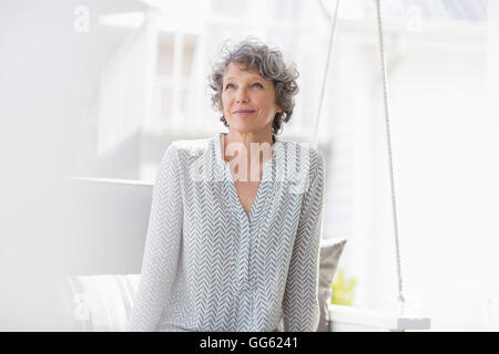 Woman sitting on a swing and thinking - Stock Photo