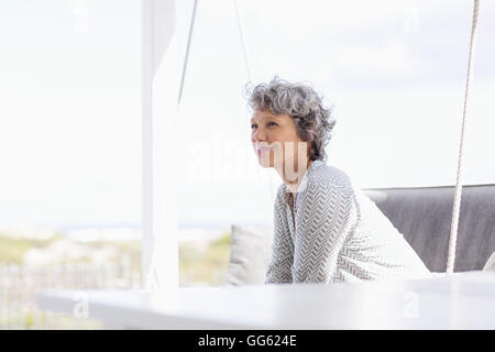 Woman sitting on a swing and day dreaming - Stock Photo