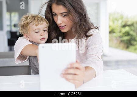 Mother and son taking selfie with digital tablet at home - Stock Photo