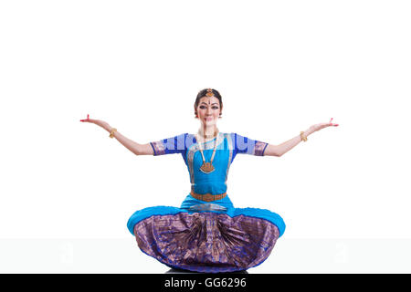 Portrait of dancer with arms outstretched performing Bharatanatyam against white background - Stock Photo