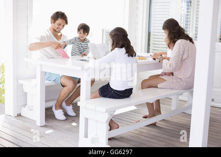 Happy young family sitting together at home - Stock Photo