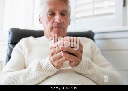 Senior man holding a cup of tea - Stock Photo
