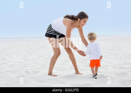 Woman playing with her son on the beach - Stock Photo