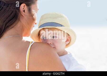 Rear view of a woman carrying her baby - Stock Photo